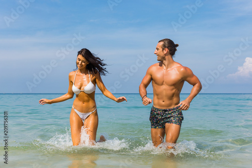 Fotografia  Happy couple laughing together holding hands running having fun splashing water in the ocean waves