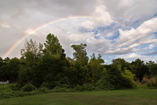 Rainbow And Blue Sky Over Green Trees And Open Lawn