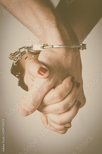 Fotografie, Obraz  Man and woman's hands handcuffed together
