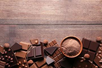 Komadići čokolade s kakaom u prahu u zdjeli na drvenom stolu