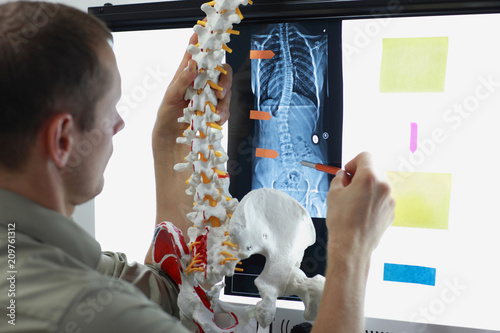expert with  model  of spine watching image of chest  at x-ray film viewer Canvas Print