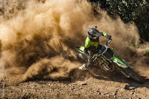 Keuken foto achterwand Motorsport Motocross rider creates a large cloud of dust and debris