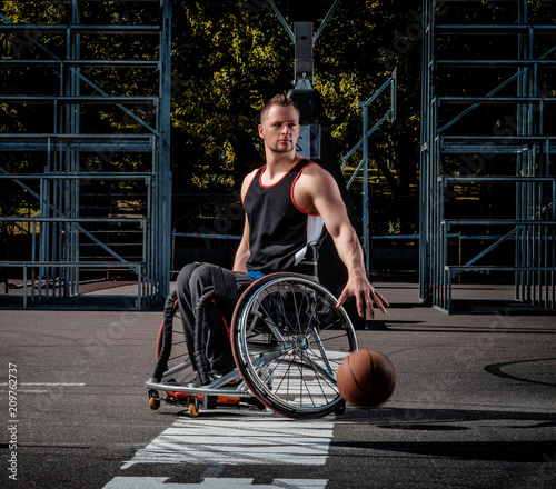 Fotografía Cripple basketball player in a wheelchair plays on open gaming ground