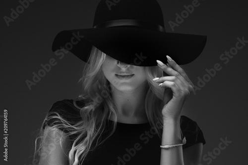 Fotografia elegant slender girl model in a stylish narrow black dress and a wide hat on a black background