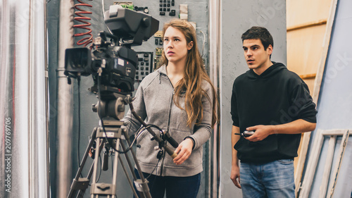 Behind the scene. Cameraman and assistant shooting film with camera