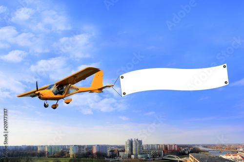 Obraz Reklama lotnicza, samolot awionetka z bilbordem reklamowym nad miastem. - fototapety do salonu