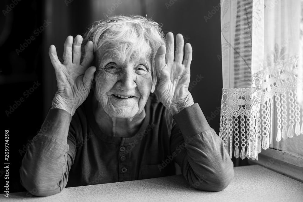 Fototapeta Portrait of cheerful old woman holding wrinkled hands near her ears. Black and white photo.