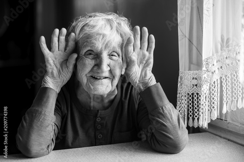 Portrait of cheerful old woman holding wrinkled hands near her ears. Black and white photo.