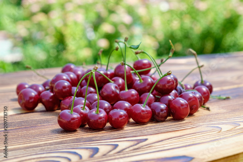Fotografie, Obraz  The heap of  ripe red cherries on the wooden table on open air