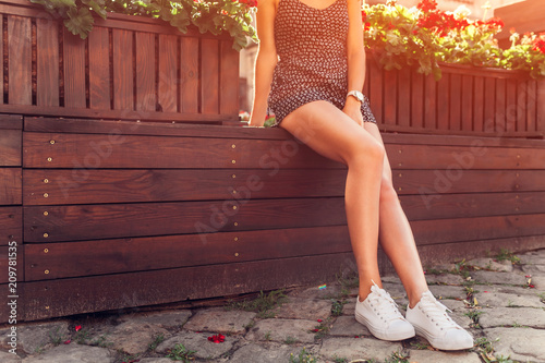 Close-up of female legs wearing sneakers outdoors. Body care concept