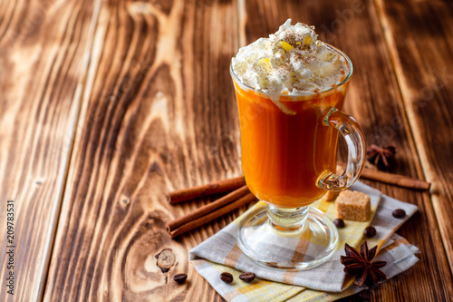 Pumpkin spice latte with whipped cream and cinnamon in glass on rustic wooden background