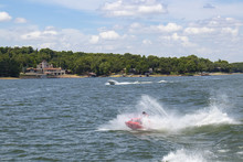 Man On Personal Water Craft Landing In A Spray Of Water After Jumping A Wake At The Lake With Speedboat And Houses And Boat Docks On Shore In The Distance