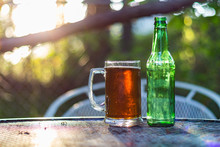 Close Up Shot Of A Beer Glass And Bottle Sitting On A Table Outside With The Sun Setting In The Background.