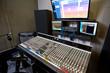 Interior shot of modern control console and monitors in contemporary music recording studio.