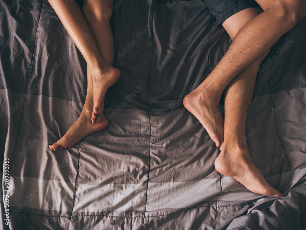 Fototapeta Close up of the legs of a couple on the bed.