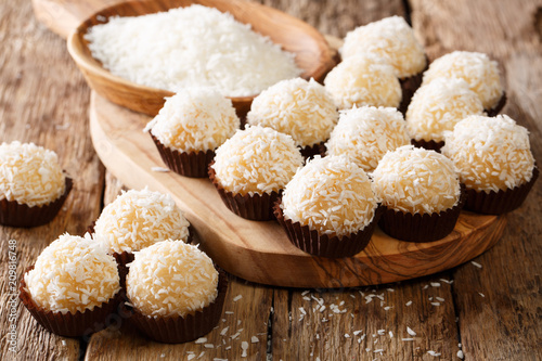 Aluminium Prints Candy Appetizing candy balls beijinhos de coco with condensed milk and coconut close-up. horizontal