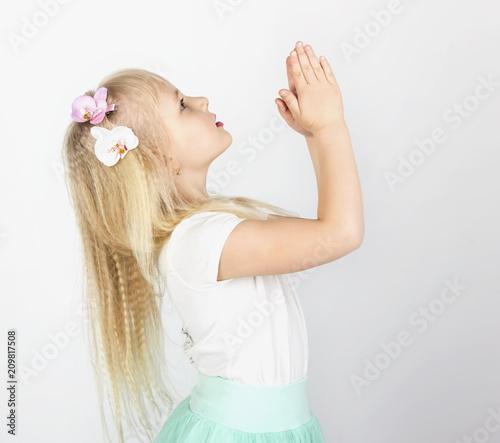 Fotografía  little blond girl folded her hands in prayer to God