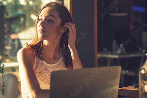 Fotografía  Beautiful attractive woman at the cafe with a laptop having a coffee break