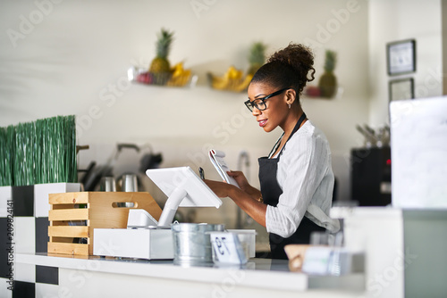 shop assistant placing order from notepad into pos point of sale terminal at reg Canvas Print