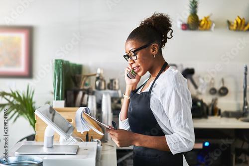 Obraz friendly waitress taking order on phone at restaurant and writing on notepad - fototapety do salonu
