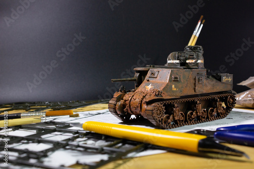 Fotografie, Obraz  Plastic model WW2 tank M3 Lee with part and tools on wooden workbench closeup