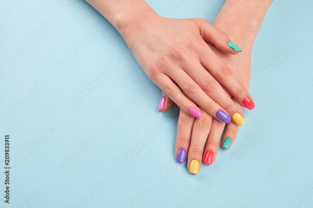 Fototapety, obrazy: Hands with beautiful manicured nails. Girl hands with beautiful summer manicure on blue background in studio. Manicured hands and copy space.