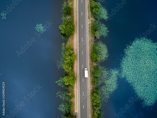 Tuinposter Luchtfoto Landscape of an asphalt road. View from above on the road going along the blue river. Summer photography with bird's eye view