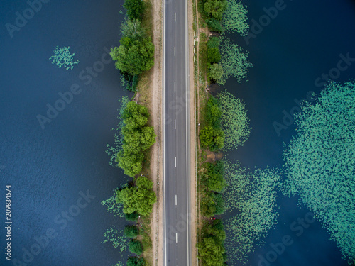 Landscape of an asphalt road. View from above on the road going along the blue river. Summer photography with bird's eye view