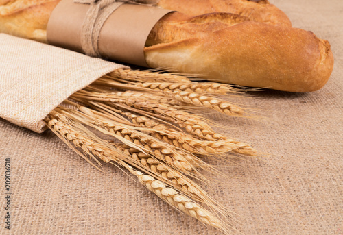 Foto op Aluminium Brood Baguette bread with wheat on sackcloth