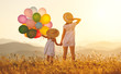 Leinwandbild Motiv happy family mother and child with balloons at sunset in summer