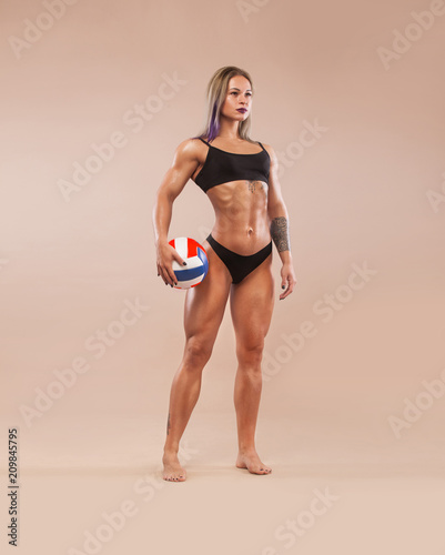Muscular young fitness sports woman with strong fit body on light background. Volleyball concept.