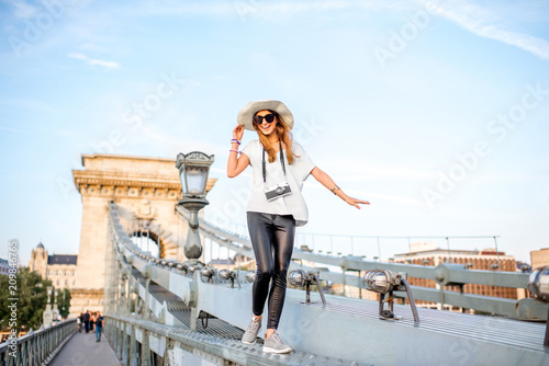 Fotografía Young woman tourist walking on the old Chain bridge during the sunset traveling