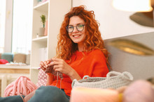 Knitting Scarf. Young Appealing Woman Wearing Stylish Black Glasses Grinning While Knitting Scarf For Her Little Niece