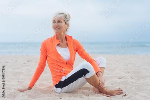Fotografie, Obraz ältere frau sitz am strand und dehnt sich nach dem sport