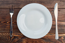 Table Setting With Plate, Fork And Knife. White Empty Plate, Silver Fork And Knife On Dark Wooden Background, Top View.
