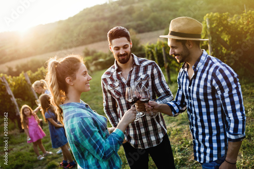 Fotografia  People tasting wine in vineyard