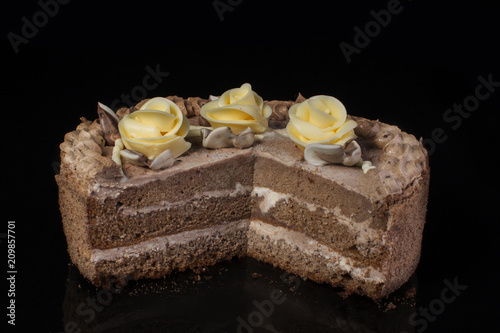 Chunk of chocolate cake decorated with oil cream on a black background