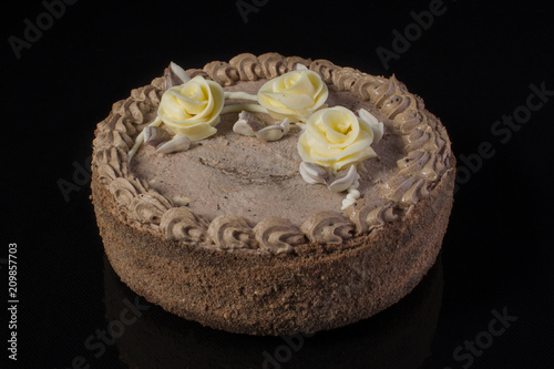 Chocolate cake with cream on a black background