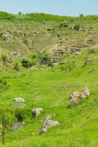 Foto op Canvas Pistache A picturesque panoramic view on green hills with rocks on a summer day in Saharna, Moldova