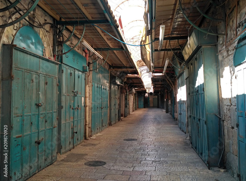 Papiers peints Les vieux bâtiments abandonnés The empty street with closed shops in the Old City of Jerusalem in the early morning.