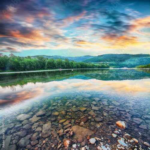 Poster Natuur Mountain river stream of water in the rocks with majestic sunset sky.