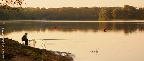 Fotografia, Obraz the fisherman catches on the lake at dawn.
