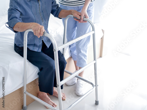 Fototapeta Croped Daughter helping her mother  using walker in bedroom. obraz