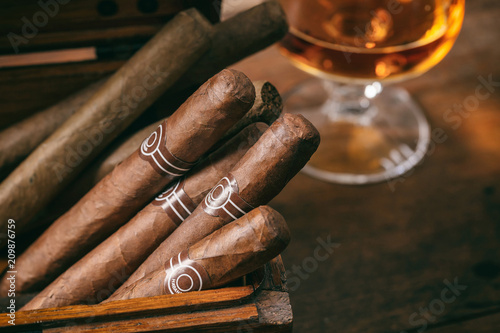 Cuban cigars closeup on wooden desk, blur glass of brandy Slika na platnu