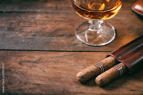 Fotografija Cuban cigars closeup on wooden desk, blur glass of brandy