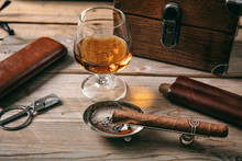 Cuban Cigar And A Glass Of Cognac Brandy On Wooden Background
