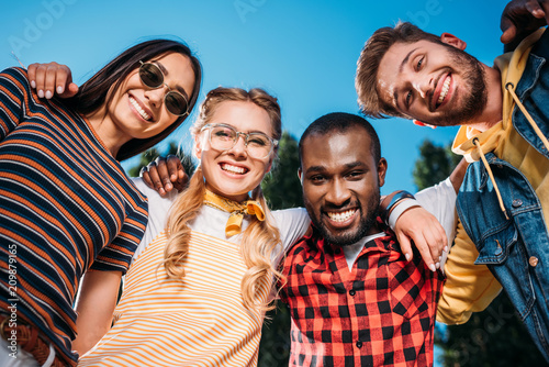 bottom view of smiling multiracial young friends looking at camera with blue sky Canvas Print