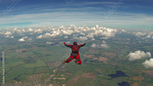 Skydiver in a red jumpsuit freefalling above the clouds