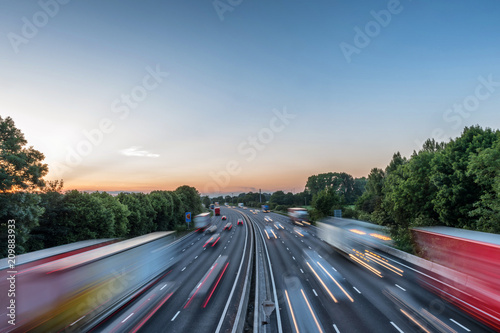 Sunset view heavy traffic moving at speed on UK motorway in England