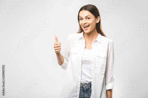 Young happy cheerful woman showing thumb up. Confident young businesswoman giving the thumbs up against a white background. Place for text.